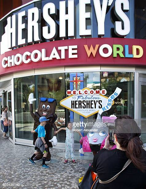 A woman photographs her children in front of Hershey's Chocolate World on the Strip in Las Vegas Nevada