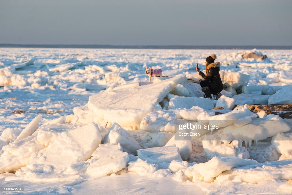 A woman photographs her English Bull Dog on a jetty next to an ice covered Cape Cod Bay near Rock Harbor on January 3, 2018 in Orleans, Massachusetts. A winter storm is hitting the east coast from Florida to New England bringing snow and frigid temperatures.