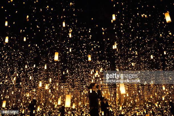 A woman photographs inside the Aftermath of Obliteration of Eternity room during a preview of the Yayoi Kusama's Infinity Mirrors exhibit at the...