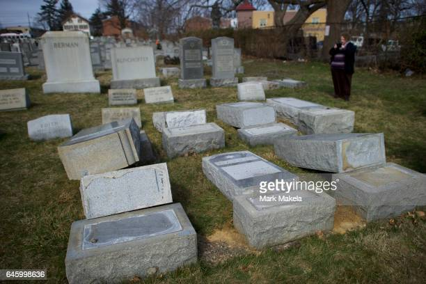 A woman photographs Jewish tombstones laying vandalized at Mount Carmel Cemetery February 27 2017 in Philadelphia Pennsylvania Police are...