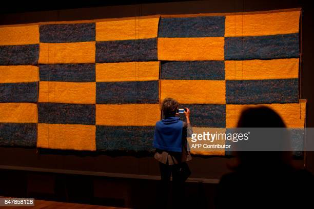 Woman photographs Peruvian feathered panels at the Getty Museum's Pacific Standard Time: LA/LA exhibit opening celebration in Los Angeles on...
