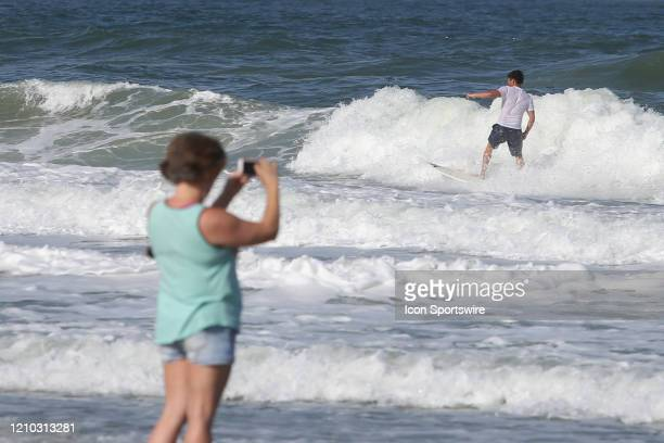 A woman photographs surfers during the beaches first open hour on April 17 2020 in Jacksonville Beach Fl Jacksonville Mayor Lenny Curry opened the...