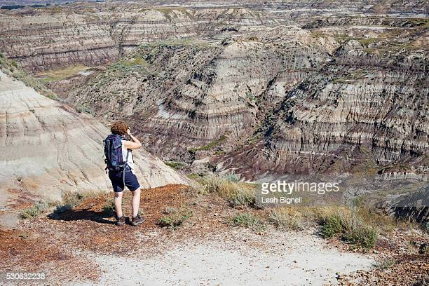 A Woman Photographs The Badlands; Drumheller, Alberta, Canada