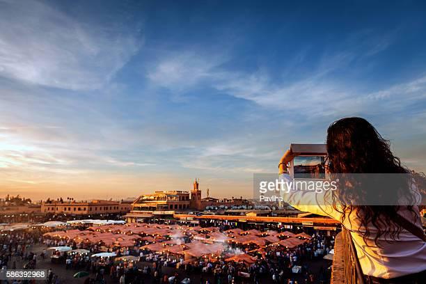 Woman photographs the market El Fna Square , Marrakech, Morocco
