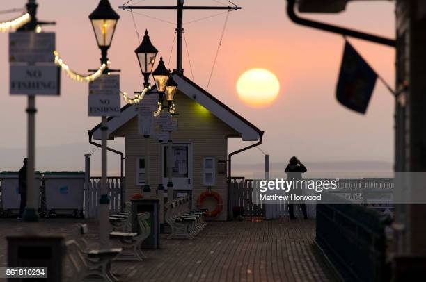 A woman photographs the sun rise at Penarth Pier as Hurricane Ophelia approaches the west coast of the United Kingdom on October 16 2017 in Penarth...