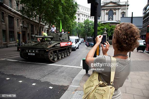 Woman photographs the tank with her mobile phone as it passes along Aldwych Campaigners and supporters from Oxfam and Amnesty International as part...