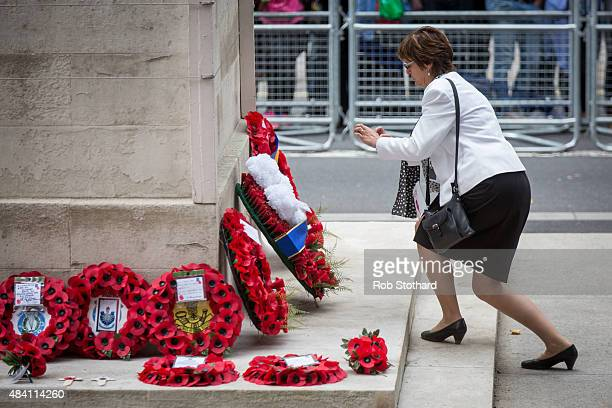 A woman photographs wreaths laid at the Cenotaph during a parade down Whitehall at the 70th Anniversary commemorations of VJ Day on August 15 2015 in...