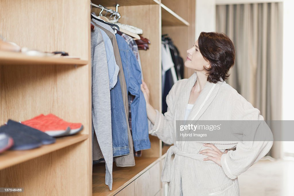 Woman picking clothes out of closet : ストックフォト
