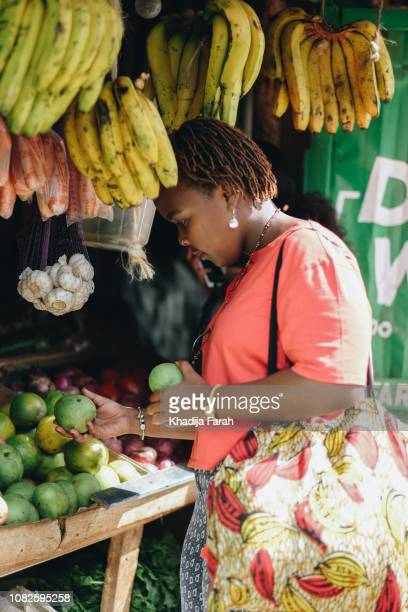 woman picking fruits at market - nairobi stock pictures, royalty-free photos & images