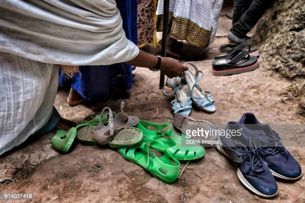 A woman picking her shoes out of a church in Lalibela During the first days of January thousands of Ethiopian Orthodox Christian pilgrims go to the...