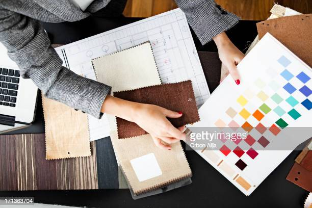 woman picking out swatches from desk - ontwerper stockfoto's en -beelden