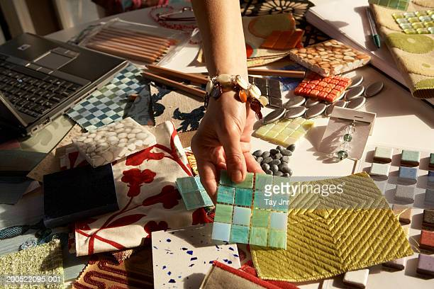 woman picking out swatches from desk - interior design foto e immagini stock