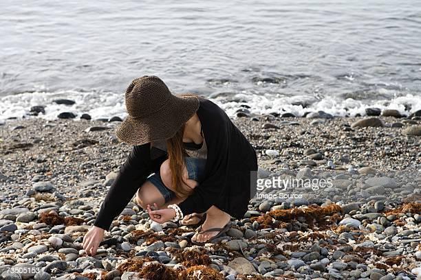 Woman picking pebbles on beach