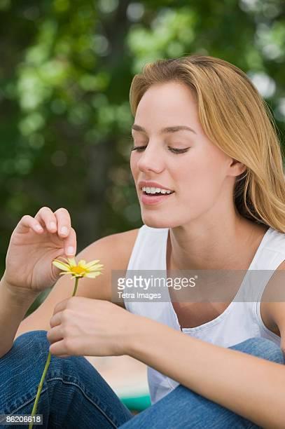 woman picking petals off flower - depilazione intima foto e immagini stock