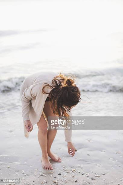 Woman picking seashells on beach