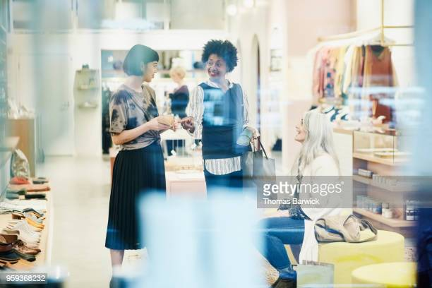 woman picking shoes while shopping with friend in clothing boutique - older women in short skirts stock pictures, royalty-free photos & images