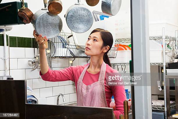 Woman picking up a cooking pan.