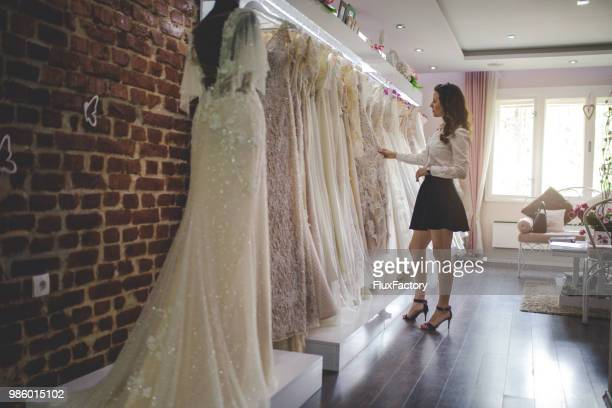 woman picking up a perfect wedding dress - wedding dress stock pictures, royalty-free photos & images