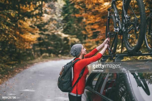 Frau, die Abholung der Fahrräder aus Auto Dachträger Abenteuer zu beginnen