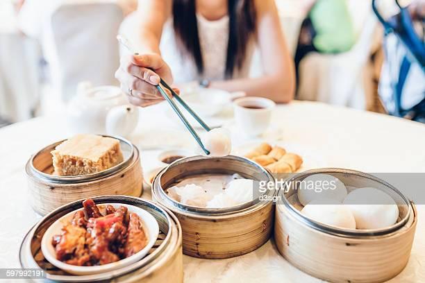 Woman picking up dim sum dumplings with chopsticks