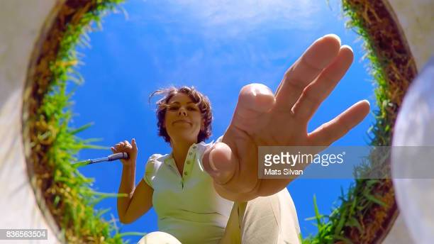 woman picking up her golf ball from the hole - low angle view stock pictures, royalty-free photos & images