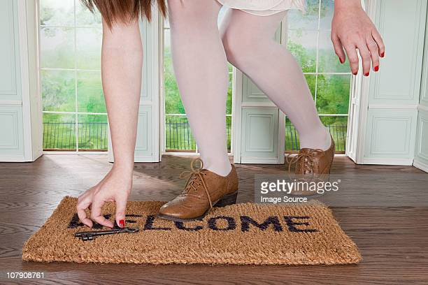 Woman picking up key on welcome mat in small room