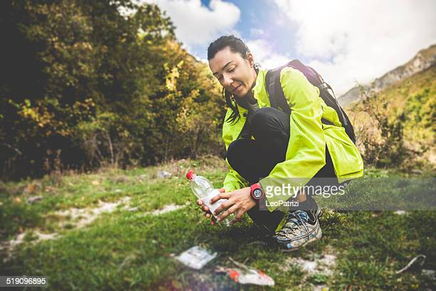 Woman picking up litter in mountain