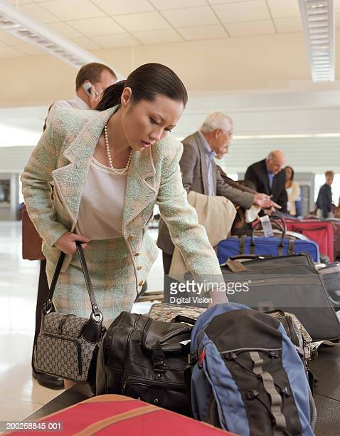 Woman picking up luggage from carousel in airport