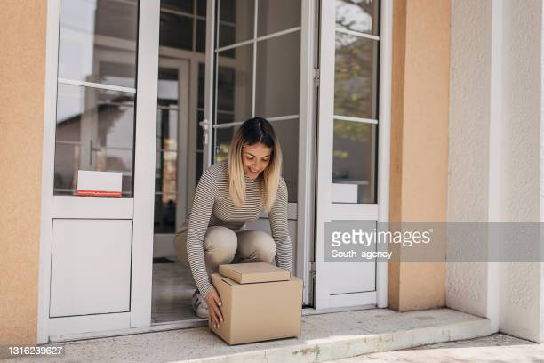 woman picking up package - picking up stock pictures, royalty-free photos & images
