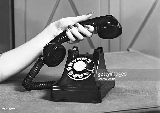 Woman picking up phone, (close up of hand), (B&W)