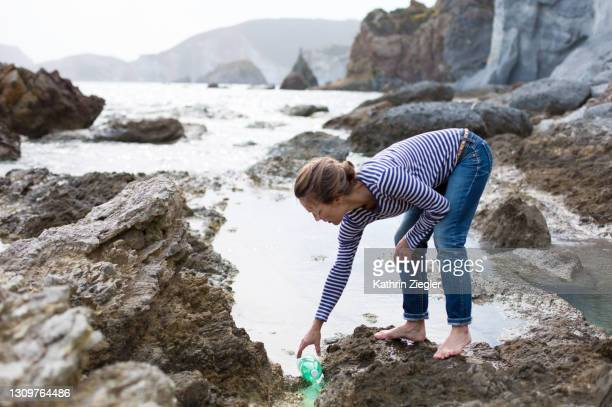 woman picking up plastic waste on rocky beach - clean stock pictures, royalty-free photos & images