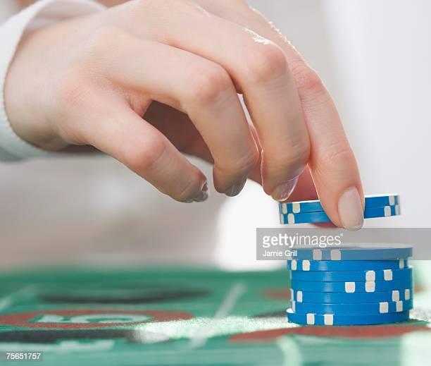 Woman picking up poker chips