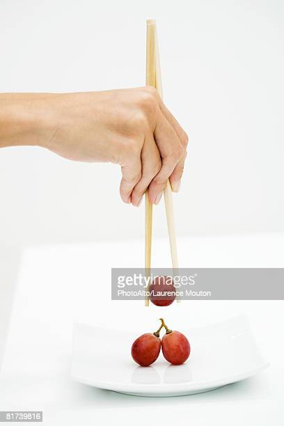 Woman picking up red grape with chopsticks, cropped view of hand