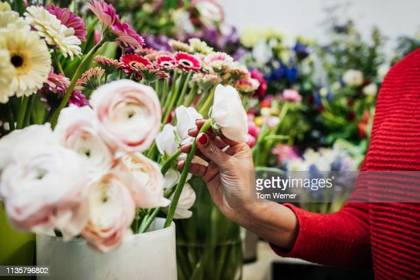 woman picking up rose while out shopping - flower head stock pictures, royalty-free photos & images