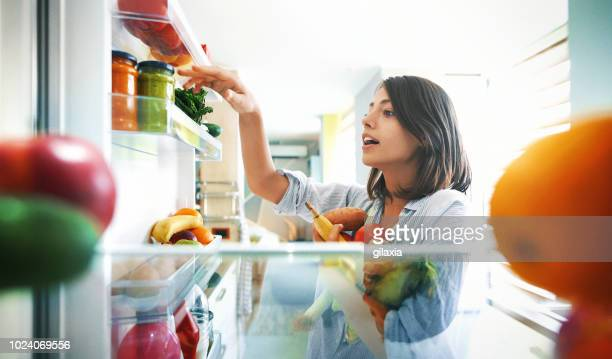 woman picking up some fruits and veggies from the fridge - cozinha doméstica imagens e fotografias de stock