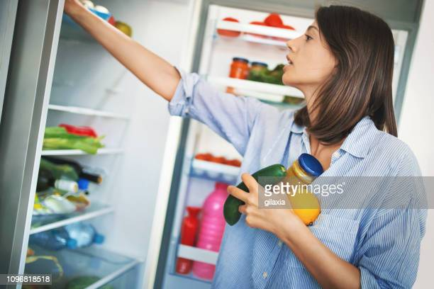 woman picking up some fruits and veggies from the fridge. - side by side stock photos and pictures