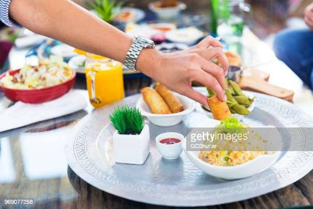 woman picking up spring roll from a chinese food platter - eid mubarak stock pictures, royalty-free photos & images