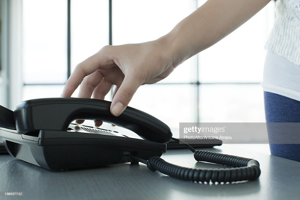 Woman picking up telephone receiver, backlit, cropped : Foto stock