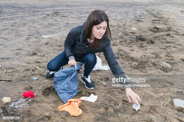 a woman picking up trash in a beach - initiative stock pictures, royalty-free photos & images