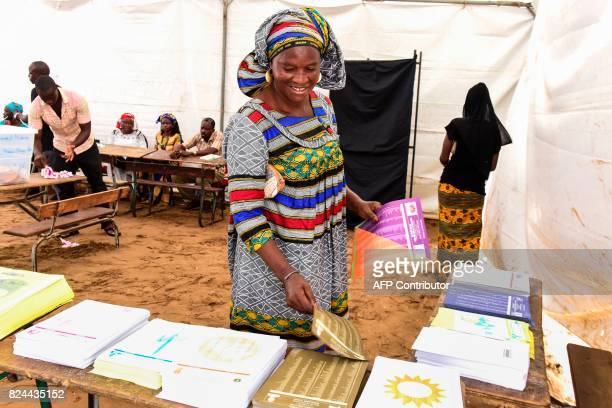 A woman picks ballot papers prior to casting her vote in Senegal's legislative election on July 30 2017 in Dakar Senegalese voters cast ballots on...