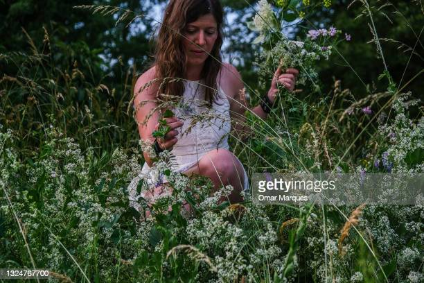 Woman picks flowers to prepare a flower crown during a Summer Solstice celebration on June 21, 2021 in Krakow, Poland. The summer solstice represents...