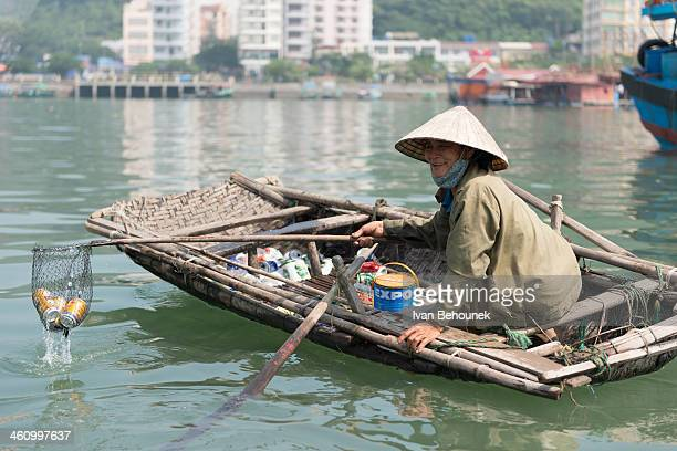 Woman picks garbage from the sea in the Cat Ba Bay and will to sell them later.