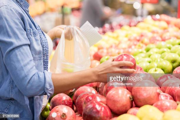 woman picks out pomegranate in supermarket - produce aisle stock photos and pictures