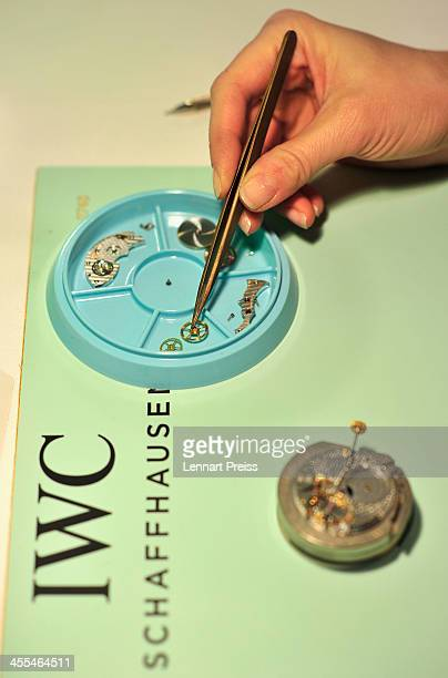 A woman picks up a piece of a clockwork with a pair of tweezers during a watchmaking class by swiss watch manufacturer IWC at The Charles Hotel on...