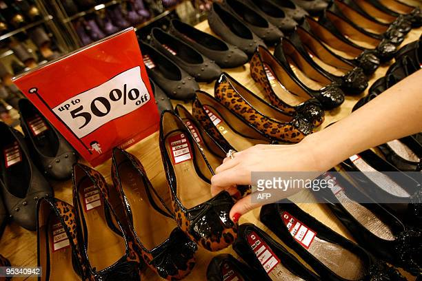 A woman picks up a shoe that is on sale as shoppers crowd in Selfridges as the store opens it doors on the first day of its winter sale on Boxing Day...