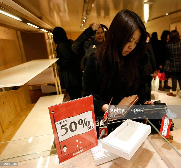 A woman picks up items that are on sale as shoppers crowd in Selfridges as the store opens it doors on the first day of its winter sale on Boxing Day...