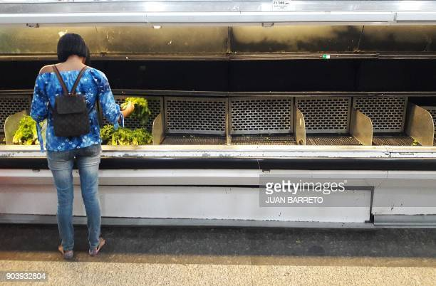 A woman picks vegetables from an almost empty refrigerated shelf at a supermarket in Caracas on January 11 2018 Colombian President Juan Manuel...