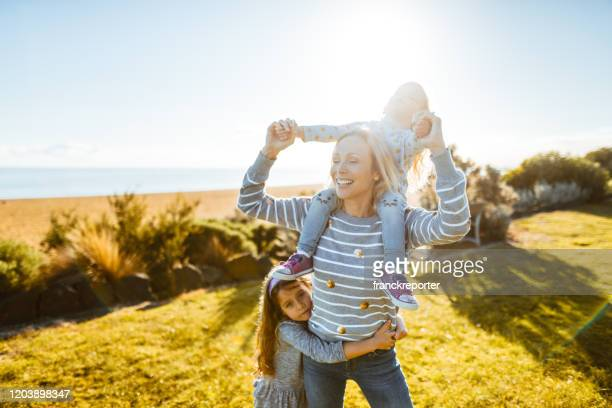 woman piggyback her daughter at summer - aunt stock pictures, royalty-free photos & images