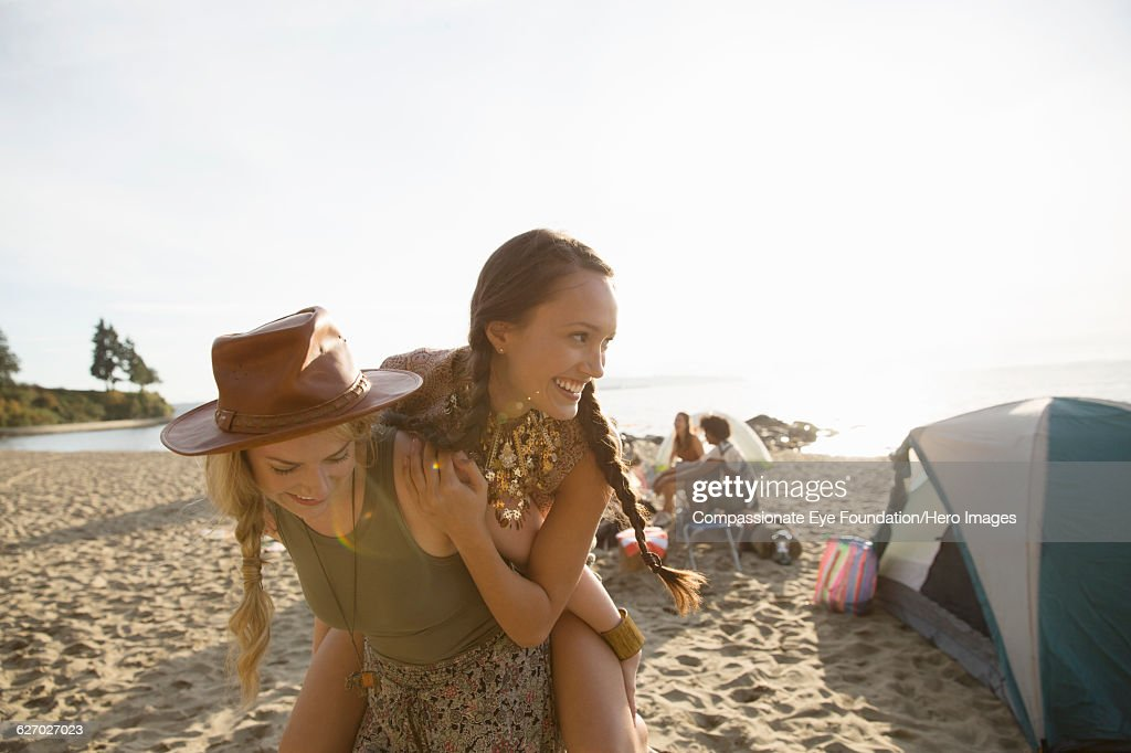 Woman piggybacking friend on beach : Stock Photo