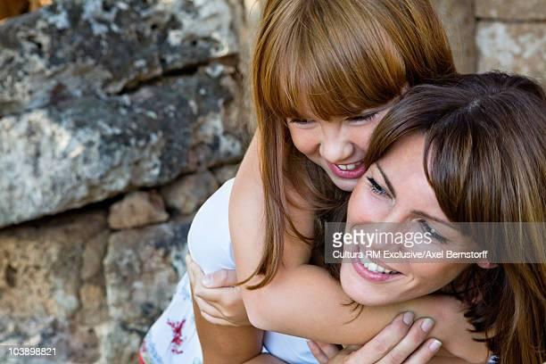 Woman piggybacking her happy daughter